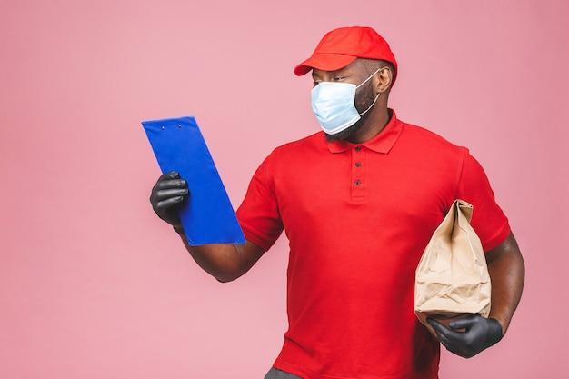Pracownik dostawy w czerwonej czapce pusty t-shirt jednolita maska na twarz rękawiczki trzymają pusty karton.