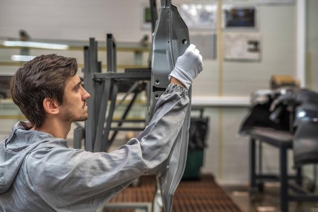 Pracownik działu jakości lakierni samochodowej sprawdza jakość nałożonej masy uszczelniającej