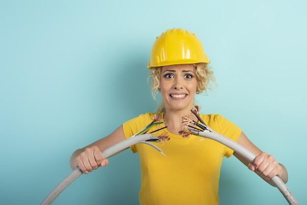Pracownik dziewczyna w kapeluszu zrywa kabel elektryczny. niebieska ściana