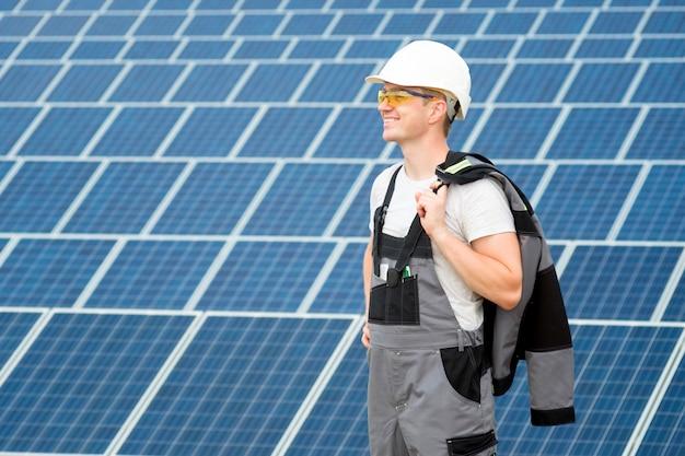 Pracownik elektryk lub inżynier w białej beczce, ochronne żółte okulary i szary strój stadnding w pobliżu pola paneli słonecznych.