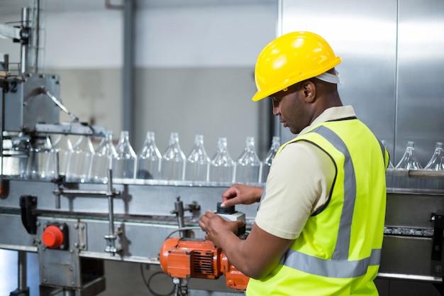 Pracownik fabryczny działająca maszyna w fabryce