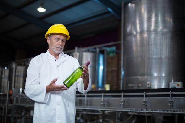 Pracownik fabryczny egzamininuje butelkę w fabryce