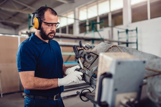 Pracownik fabryczny obsługujący przecinarkę taśmową
