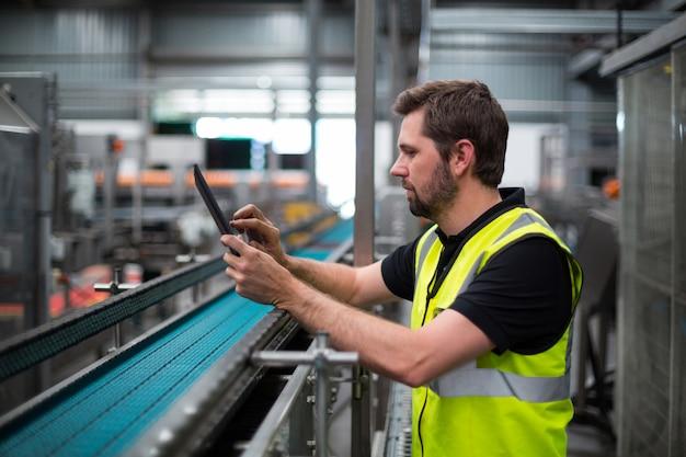 Pracownik fabryczny używa cyfrową pastylkę w fabryce