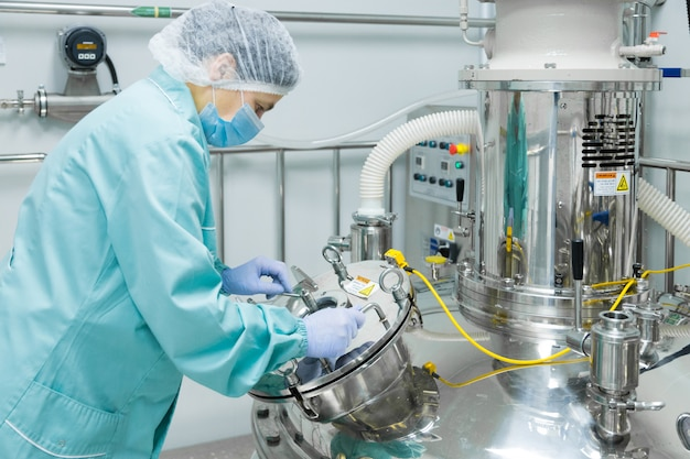 Pracownik fabryki farmaceutycznej w odzieży ochronnej obsługującej linię produkcyjną w sterylnym środowisku