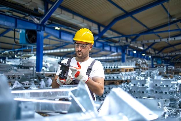 Pracownik fabryki pracujący w przemysłowej hali produkcyjnej