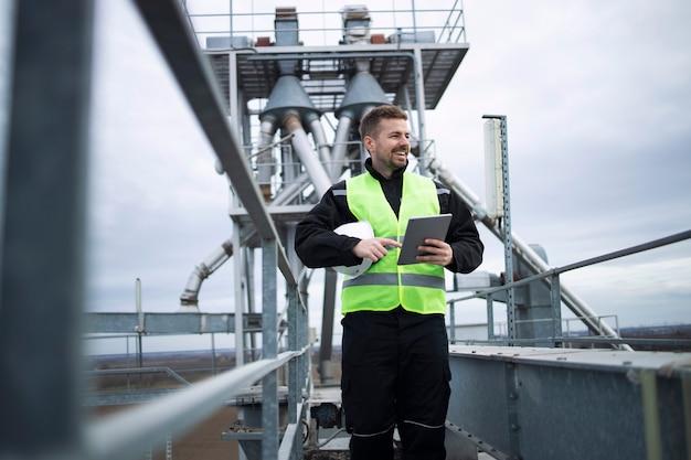 Pracownik fabryki przemysłowej stojący na wysokiej metalowej konstrukcji zakładu produkcyjnego