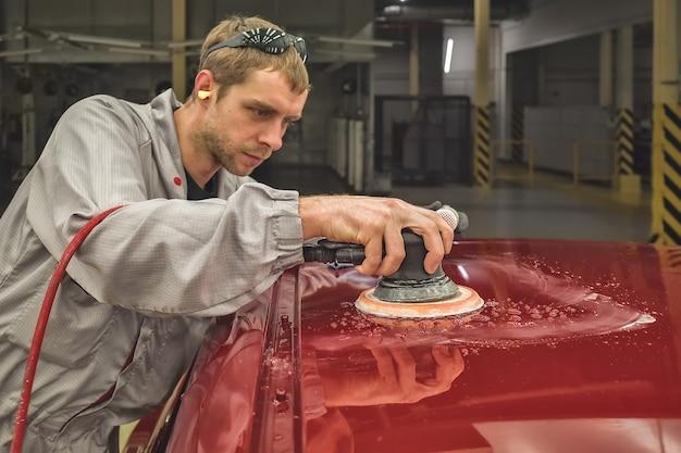 Pracownik fabryki samochodów szlifuje nadwozie narzędziem pneumatycznym