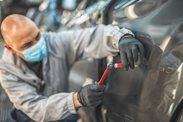 Pracownik fabryki samochodów w ochronnej masce medycznej usuwa ręcznym narzędziem niewielki ubytek metalu.