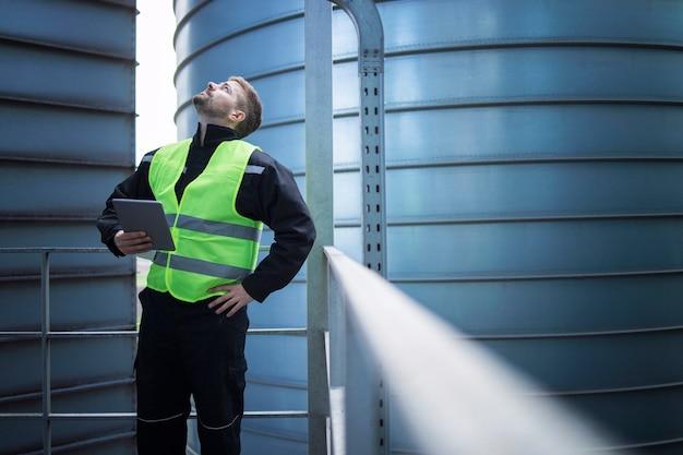 Pracownik fabryki stojący na metalowej platformie między przemysłowymi zbiornikami magazynowymi i spoglądający w górę w celu oględzin silosów do produkcji żywności