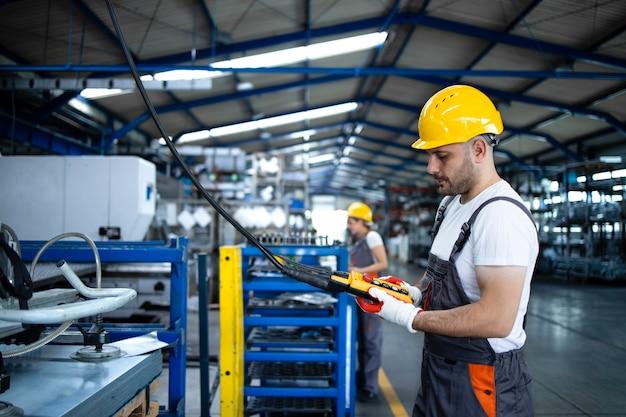 Pracownik fabryki ubrany w mundur i kask obsługujący maszynę przemysłową z joystickiem z przyciskiem w hali produkcyjnej