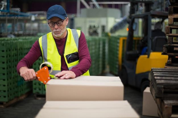 Pracownik fabryki uszczelnia kartony