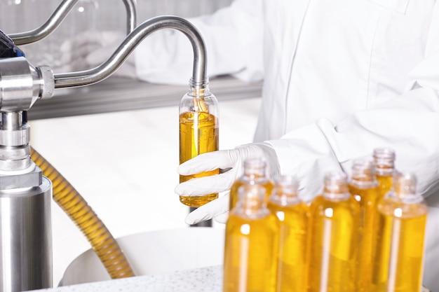 Pracownik fabryki w białej sukni i gumowych rękawiczkach trzyma plastikową butelkę