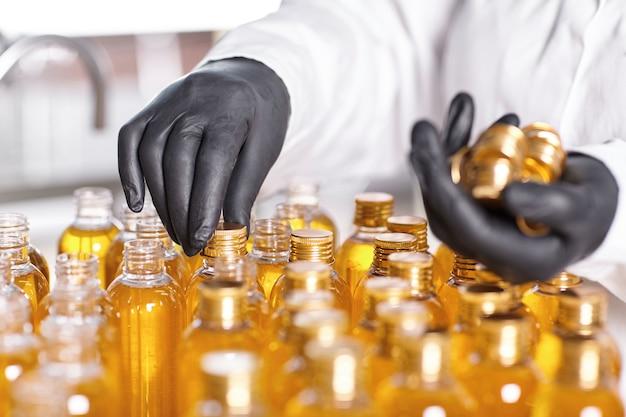 Pracownik fabryki w białej sukni i gumowych rękawiczkach zakręcający nakrętki do butelek
