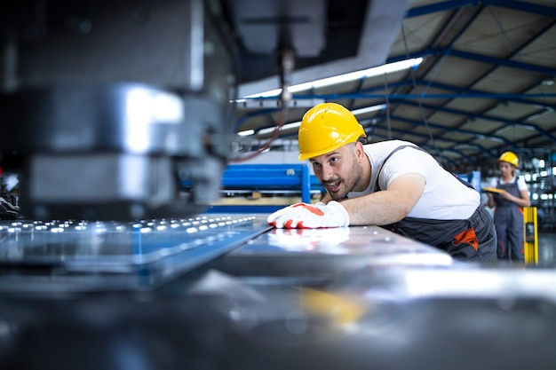 Pracownik fabryki w mundurze ochronnym i kasku obsługującym maszynę przemysłową na linii produkcyjnej