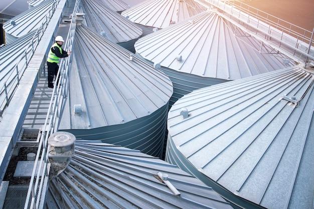Pracownik fabryki w odzieży ochronnej chodzący po elewatorze zbożowym i obserwujący dachy silosów.