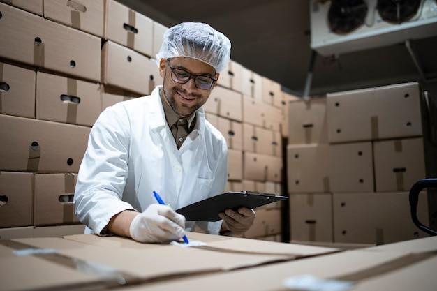 Pracownik fabryki w siatce na włosy i rękawiczkach higienicznych przygotowujący opakowania świeżej żywności do dystrybucji i sprzedaży rynkowej.