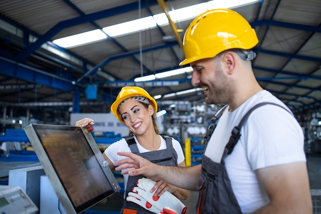 Pracownik fabryki wyjaśniający praktykantowi, jak obsługiwać maszynę przemysłową przy użyciu nowego oprogramowania na komputerze z ekranem dotykowym