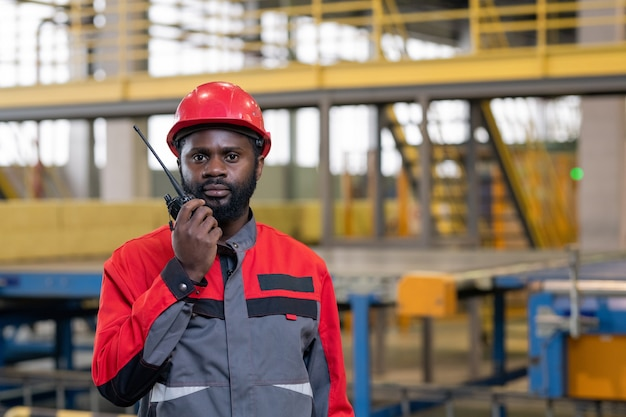 Pracownik fabryki za pomocą zestawu radiowego