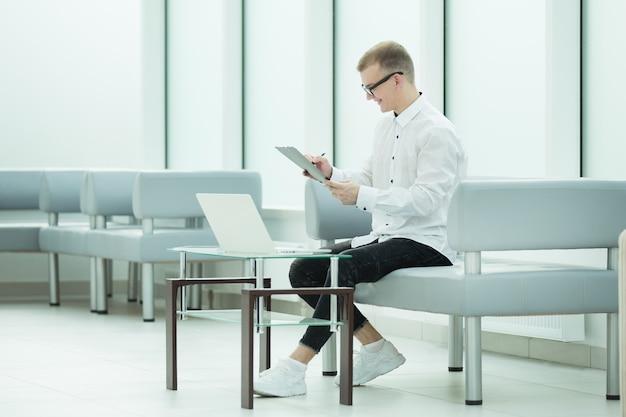 Pracownik firmy czyta dokument biznesowy siedząc w holu biura. zdjęcie z miejscem na kopię