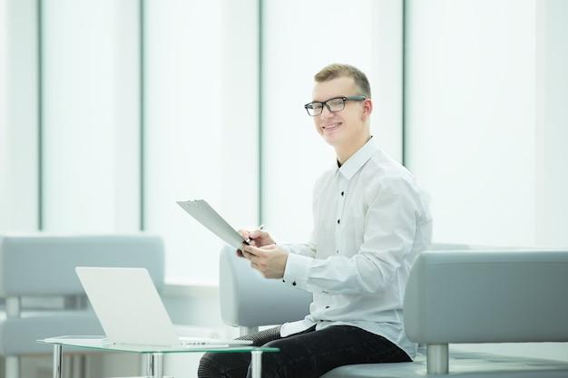 Pracownik firmy czyta dokument biznesowy siedząc w holu biura