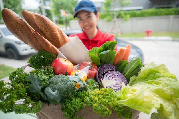 Pracownik firmy dostawczej trzymający torbę na zakupy, zamówienie żywności, usługa supermarketu, przyjmujący pudełko z artykułami spożywczymi od kobiety dostarczającej w domu, dostawa świeżych organicznych warzyw