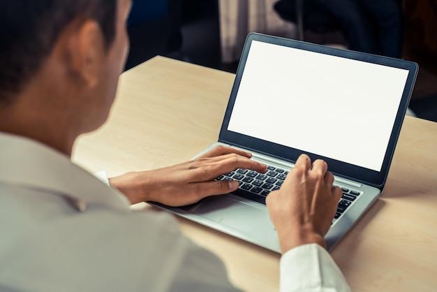 Pracownik firmy osoba korzysta z komputera przenośnego.