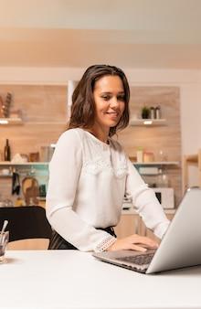Pracownik firmy patrząc na komputer stacjonarny laptopa pracuje w ważnym terminie. skoncentrowany przedsiębiorca w domowej kuchni korzystający z notebooka w późnych godzinach wieczornych.
