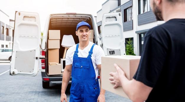 Pracownik firmy przenoszącej rozładunek pudełek z minibusa do domu klienta