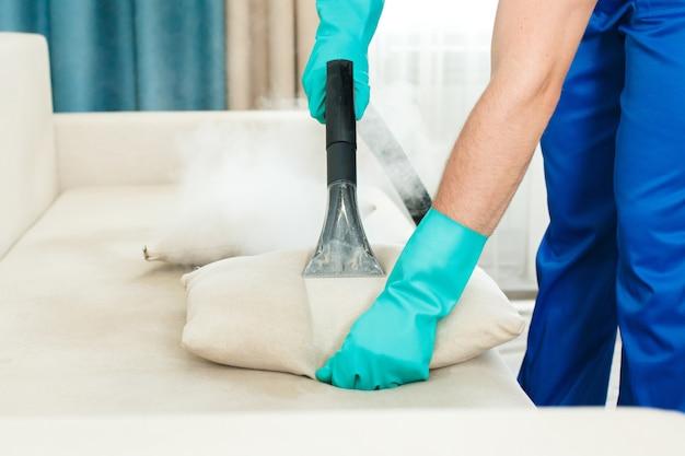 Pracownik firmy sprzątającej świadczy usługi czyszczenia chemicznego i parowego sofy.