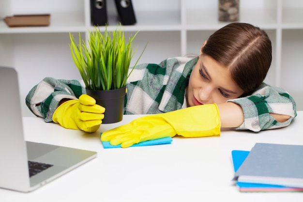 Pracownik firmy sprzątającej w kombinezonach i żółtych rękawiczkach sprząta biuro