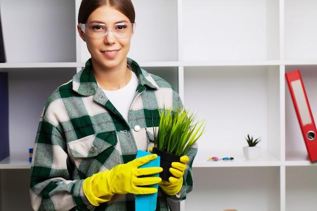 Pracownik firmy sprzątającej wyciera kurz z roślin.