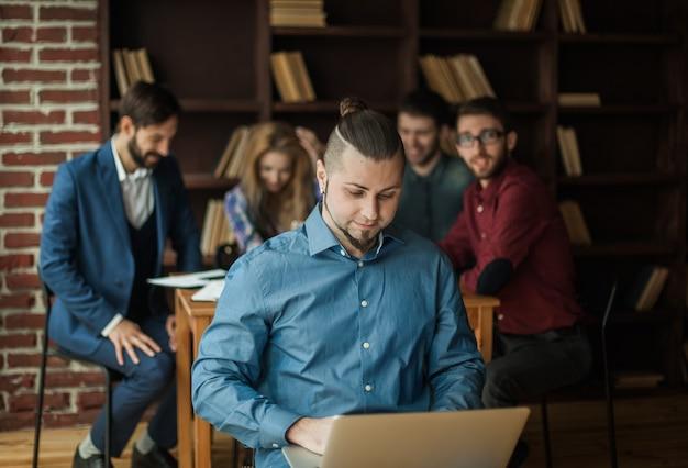 Pracownik firmy z laptopem na tle pracy zespołu biznesowego w biurze