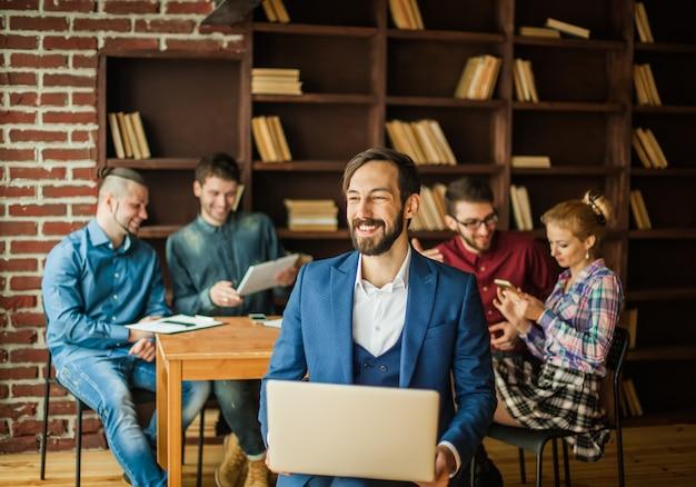 Pracownik firmy z laptopem oraz zespół biznesowy omawiający bieżące problemy firmy