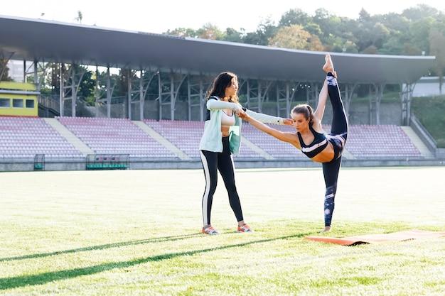Pracownik fizjoterapeuty robi leczenie swojej klientce fitness kobieta w odzieży sportowej z trenerem