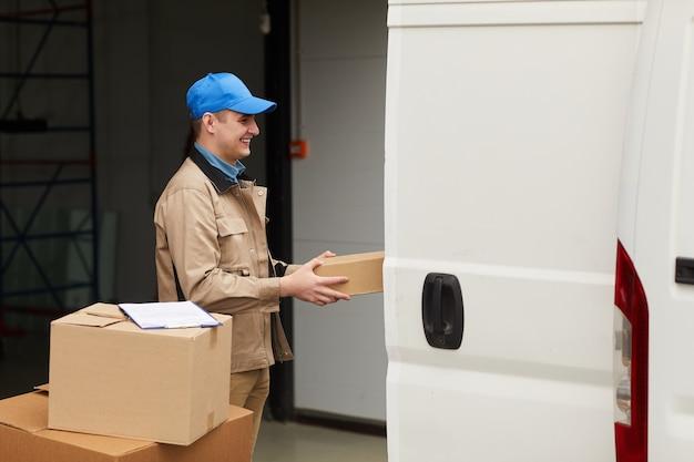 Pracownik fizyczny niosący pudełka i ładujący je do furgonetki w magazynie