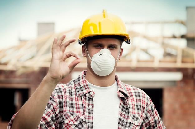 Pracownik fizyczny z kaskiem i maską ochronną