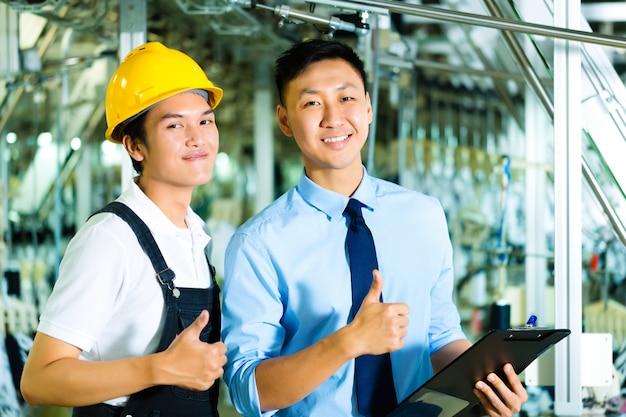 Pracownik i kierownik produkcji ze schowkiem