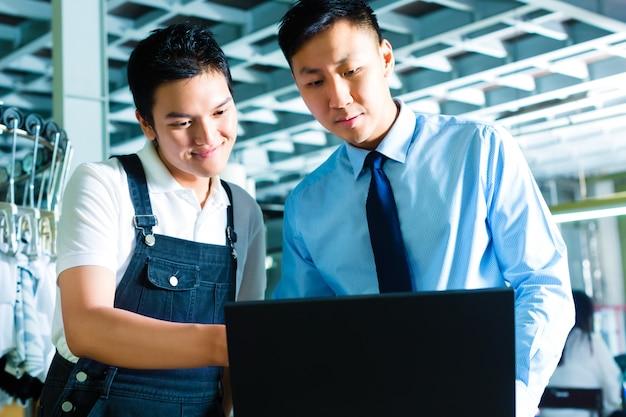Pracownik i przełożony z laptopem w fabryce