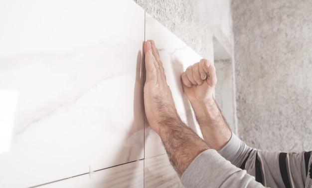Pracownik instalujący płytki na ścianie