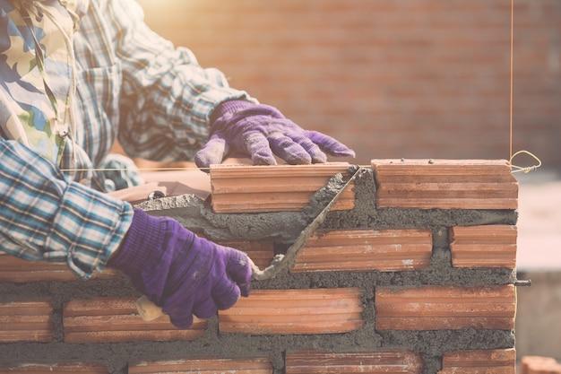 Pracownik instaluje cegły ścianę w trakcie domowego budynku