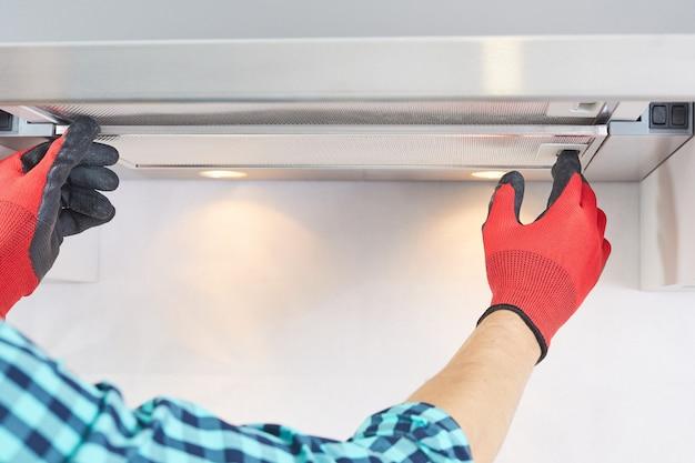 Pracownik instaluje filtr w okapie domowym w kuchni. złota rączka wyjmująca filtr z okapu. naprawa okapu kuchennego.