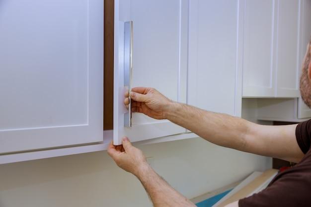 Pracownik instaluje nowy uchwyt na białej szafce