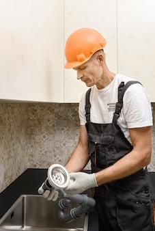 Pracownik instaluje odpływ ściekowy do zlewu kuchennego.