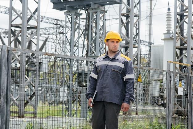 Pracownik inżyniera oprowadza i przegląda nowoczesną podstację elektryczną. energia. przemysł.