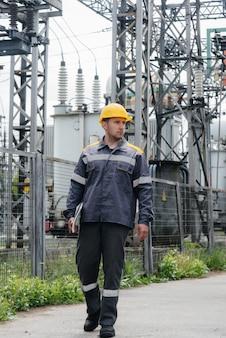 Pracownik inżyniera oprowadza i przegląda nowoczesną podstację elektryczną.