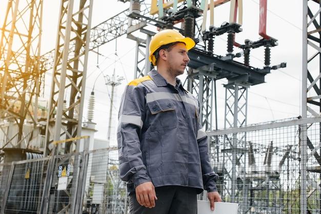 Pracownik inżynierski dokonuje oględzin i inspekcji nowoczesnej stacji elektroenergetycznej. energia. przemysł.