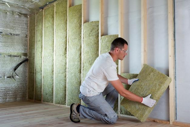 Pracownik izolujący wełnę mineralną w drewnianej ramie na przyszłe ściany domu jako bariera zimna.