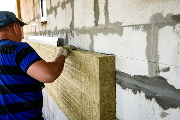 Pracownik izoluje dom płytami z wełny mineralnej. wewnętrzne ocieplenie ścian wełną mineralną.