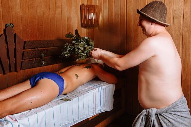 Pracownik kąpieli unosi się nad dębową miotłą klienta